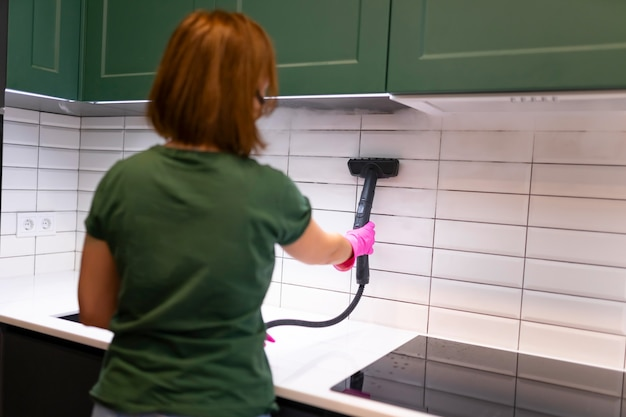 Woman cleaning tiles in the kitchen