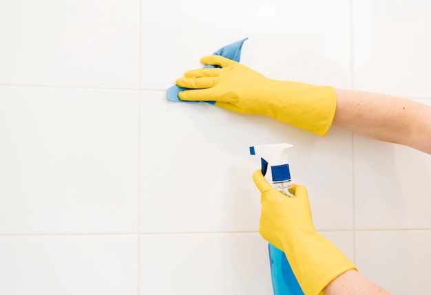 Woman cleaning wall tiles