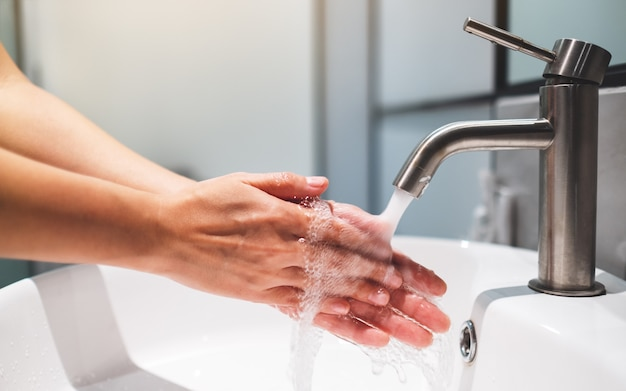 Woman cleaning and washing hands under the faucet in bathroom