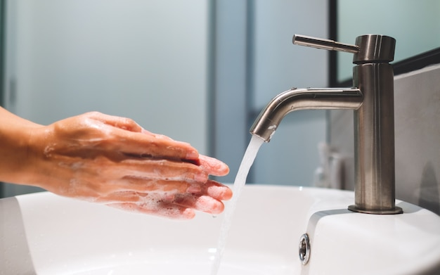 Woman cleaning and washing hands with soap under the faucet in bathroom