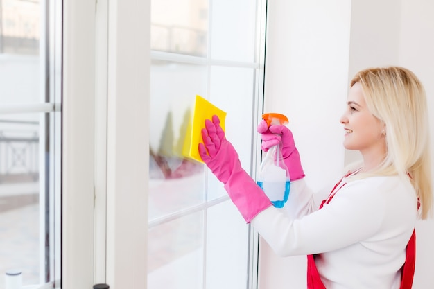 Woman cleaning windows at home with detergents cleaner