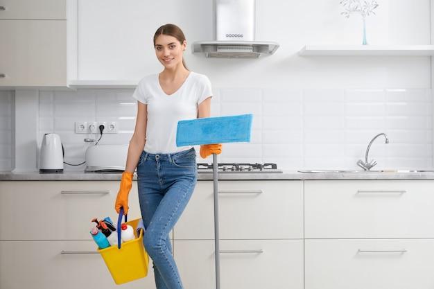 Женщина, убирающая моющее средство на кухне