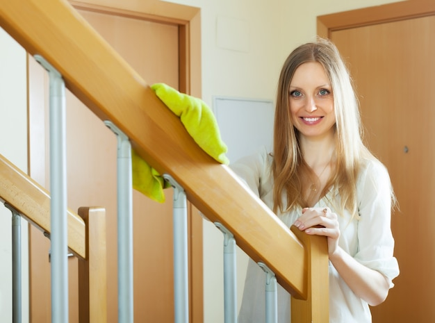 Woman cleaning wooden stair railings at home