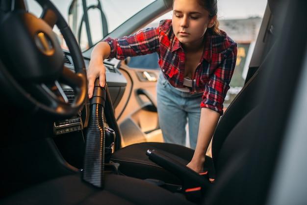 Женщина чистит салон автомобиля с помощью пылесоса, автомойки. дама с пылесосом на автомойке самообслуживания. уборка автомобилей на открытом воздухе в летний день