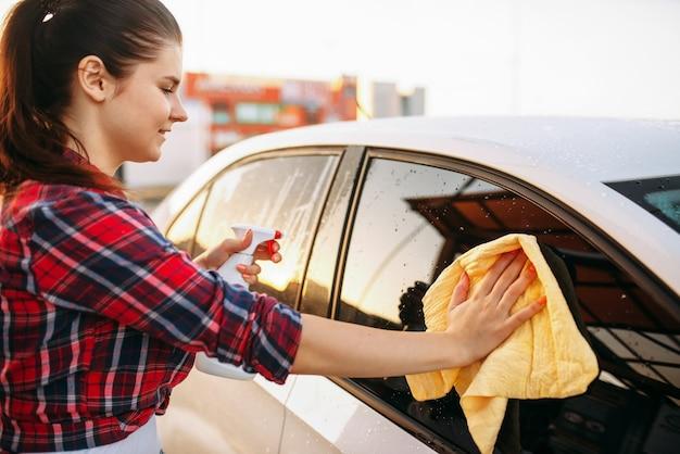 Женщина чистит переднее стекло автомобиля спреем
