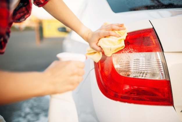 Woman cleans rear lights of the car with spray