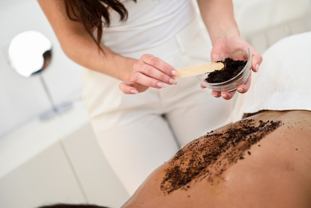 Woman cleans skin of the body with coffee scrub in spa wellness center.