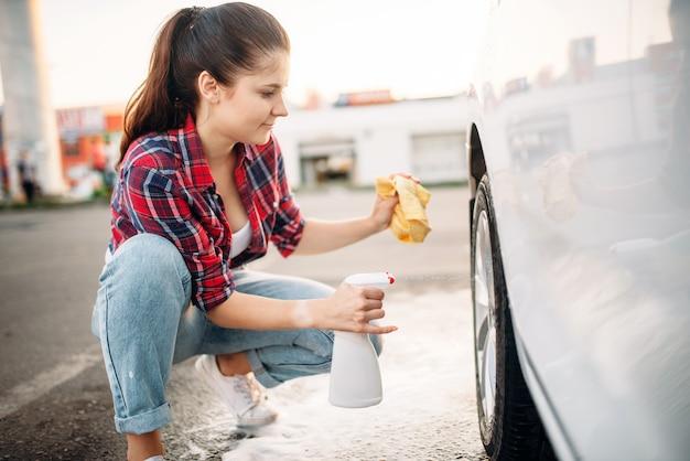 Женщина чистит колесный диск автомобиля спреем, автомойка. дама на самообслуживании автомойки. уборка автомобилей на открытом воздухе в летний день