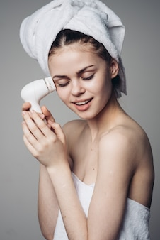 Woman cleansing face massage brush