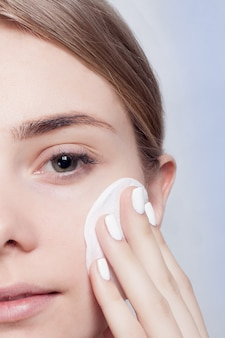 コットンで洗顔する女性