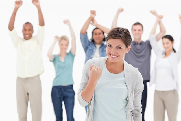 後ろにいる人々と拳を握っている女性