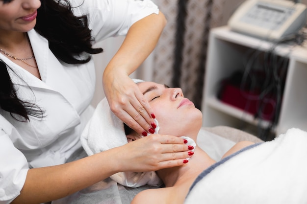 Woman client in salon receiving manual facial massage from beautician
