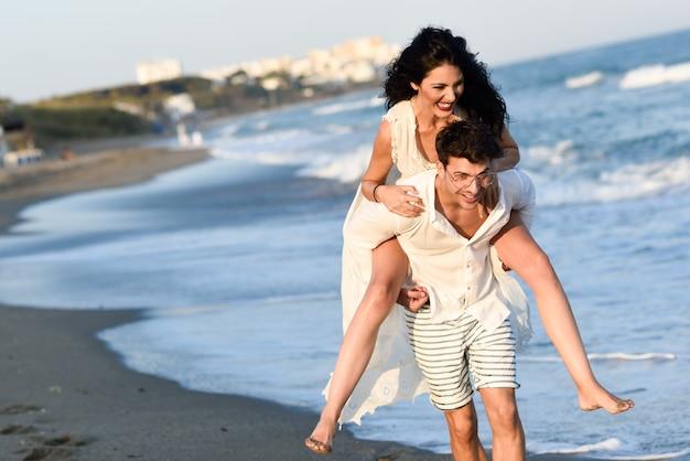 여자는 해변에서 남자의 등에 올라