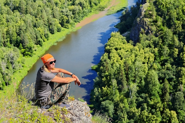 Woman climbed to top of mountain and rests, at foot of the cliff  river flows,  sunny summer day.