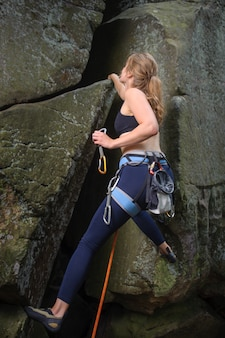 Woman climber climbing a big rock and holding carbines.