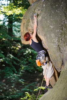Woman climber climbing rocky wall and clipping carbine
