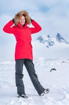 赤い冬の防風ジャケットを着て、地平線上のロッキー山脈を背景に雪の中に立って、頭の上にボンネットをかざす女性登山家。屋外でポーズをとる魅力的な笑顔のスポーティな女性
