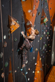Woman climber is climbing up on indoor climbing wall and looking up