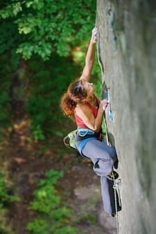 Woman climber looking for next grip on challenging rock wall on high altitude with rope
