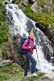 壮大な滝の近くの岩の上でポーズ女性登山家
