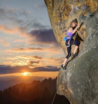 Woman climbing challenging route with rope and carbines
