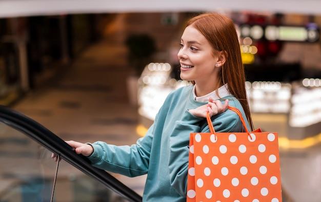 Woman climbing escalator and holding paper bag