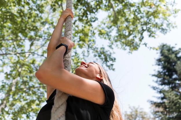Женщина, поднимающаяся по веревке