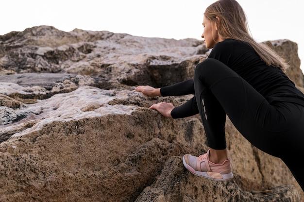 Женщина, перелезающая через скалы