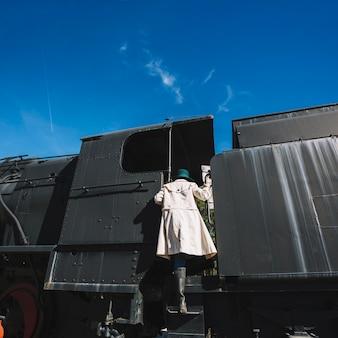 Woman climbing on retro train