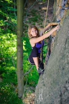 Woman climbing on a rock wall with rope and carbines engaged