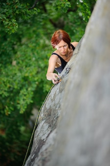 Woman climbing steep cliff wall in summer time belaying herself