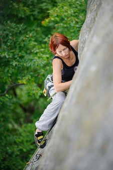 Woman climbing steep cliff wall in summer time