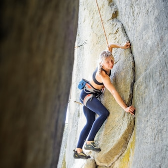 Woman climbing steep stone wall in nature, with rope