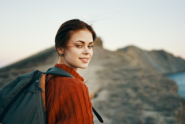 Woman climbs the mountains along the path and a backpack on her back side view. high quality photo