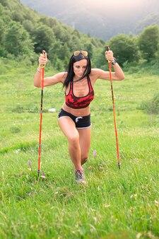 여자는 막대기를 사용하여 가파른 산길을 올라