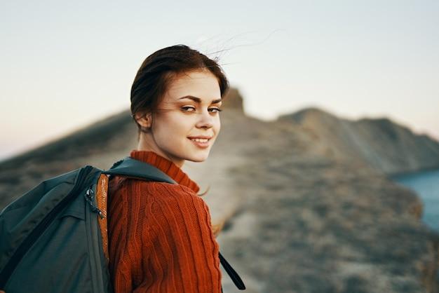女性は小道に沿って山を登り、後ろ側からバックパックを眺めます。高品質の写真
