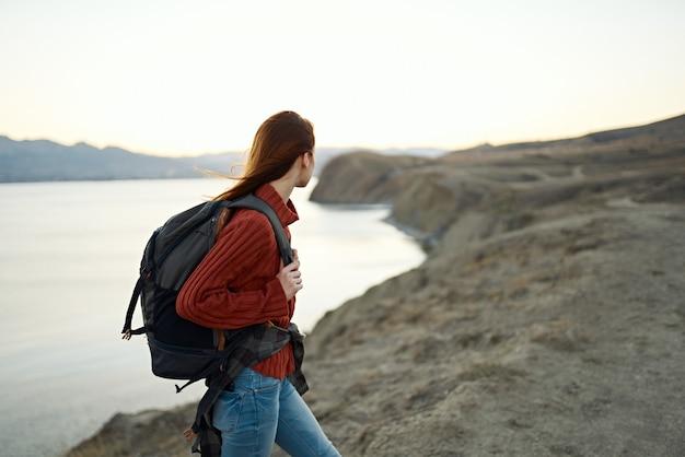 Женщина поднимается в горы и смотрит на море вдалеке пейзаж облака путешествия туризм. фото высокого качества