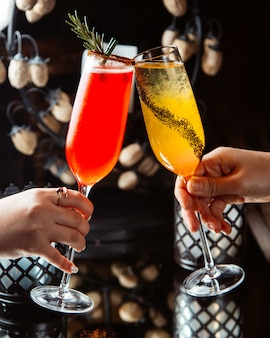Woman clink champagne glasses with citrus cocktails