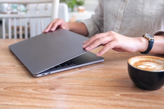 Женщина закрыть и открыть портативный компьютер на столе после завершения его использования