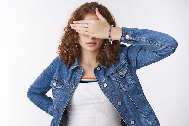 Woman close eyes performing blindness pose hide sight with palm look serious unwilling see, promise not peek. waiting for command, standing white background wearing denim jacket