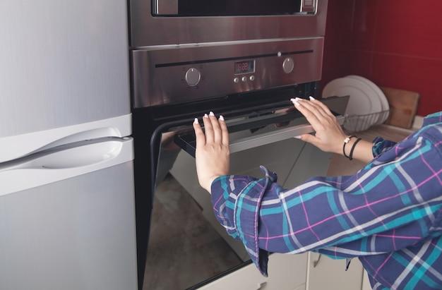女性は台所のオーブンのドアを閉めます。