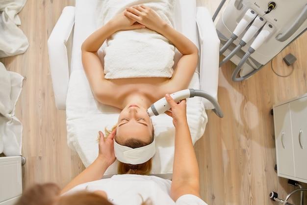 Женщина заделывают, получая электрический массаж лица на оборудовании для микродермабразии в салоне красоты.