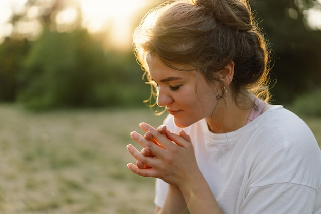 Женщина закрыла глаза, молясь в поле во время красивого заката, руки сложили в молитвенной концепции для ...