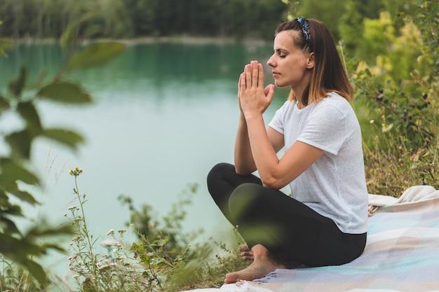 女性は屋外で祈りながら目を閉じた。信仰、霊性、宗教の祈りの概念に折り畳まれた手