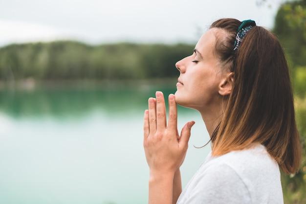 Женщина закрыла глаза, молится на открытом воздухе. руки, сложенные в молитвенной концепции веры, духовности и религии