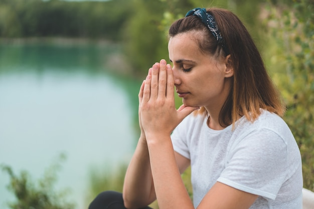 Woman closed her eyes, praying in outdoors. hands folded in prayer concept for faith, spirituality and religion