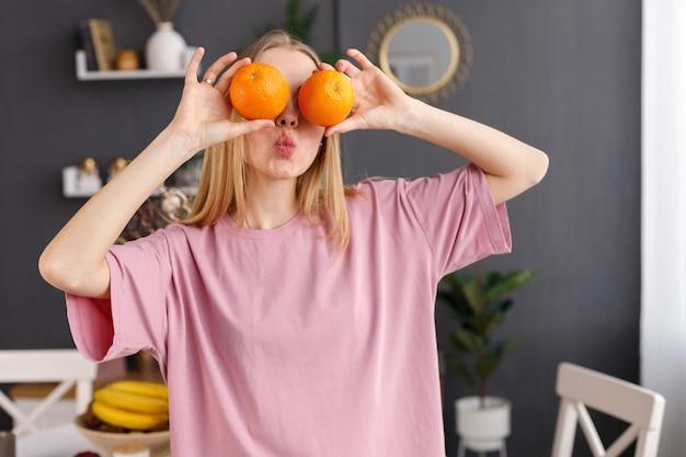 여자는 집에서 오렌지와 함께 그녀의 눈을 감고
