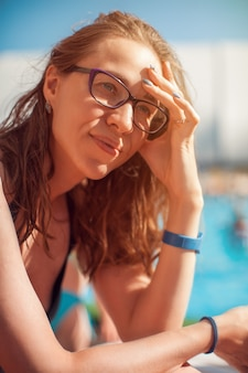 Woman closeup portrait relaxing by pool
