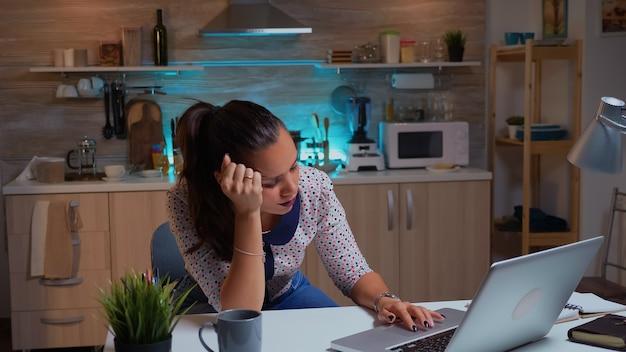 여자는 밤늦게 작업을 위한 프로젝트를 하는 동안 피로 때문에 눈을 감고 있습니다. 현대 기술 네트워크를 사용하여 노트북에서 책을 읽으며 잠에서 깨어나면서 피곤한 원격 직원
