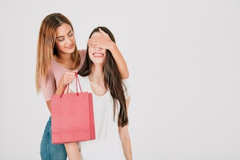 Woman closing eyes to girlfriend for paper bag gifting